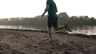 Super slow motion steadicam video of athletic man running on sandy riverside, 240 fps