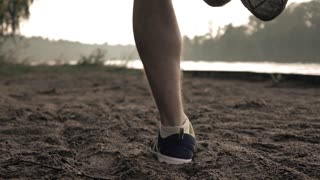 Super slow motion steadicam video of runner's feet on sandy riverside, 240 fps