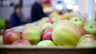 Supermarket - customers select apples in fruit Department, defocused
