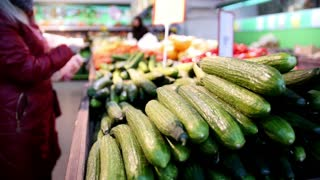 Supermarket - customers select cucumbers in vegetable Department, defocused