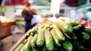 Supermarket - shopers select cucumbers in vegetable Department, defocused