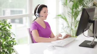 Support phone operator in headset at workplace using personal computer looking at camera and smiling