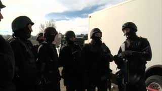 Swat Team Confers Near White Trailer On Film Set