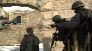 Swat Team Files Past Stone Doorway On Film Set