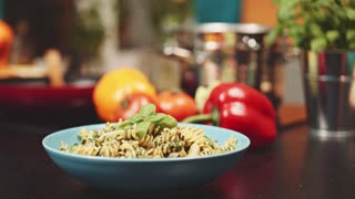 sweet basil leaf on pasta, Slow Motion 120 fps, dolly shot. Pasta with green basil leaf at the kitchen background. Delicious food, home cooking. 4K