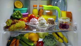 Sweet cakes in the open refrigerator. Products in the refrigerator.