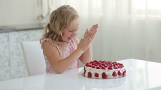 Sweet little girl getting ready to eat a strawberry cake