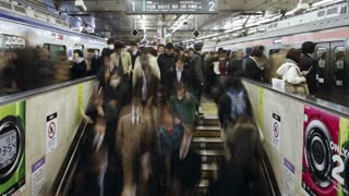 T/L Commuters tmoving on an escalator in Shibuya Station at rush hour, Shibuya, Tokyo, Honshu, Japan