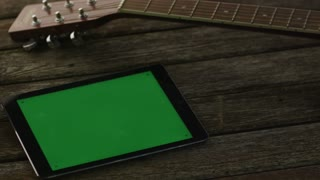 Tablet PC with Green Screen Laying on Wooden Table next to Guitar and Headphones. Causal Lifestyle