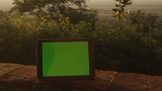 Tablet PC with Green Screen Staying Outdoors.