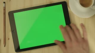 Tablet with Green Screen Laying on a Wooden Table in Landscape Mode.