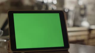 Tablet with Green Screen Staying on a Table