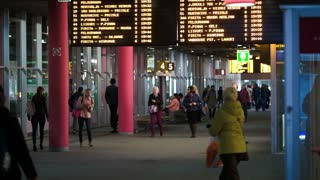 TALLIN, ESTONIA - MAY 25, 2014: People walking on Central bus station with digital display with routes above