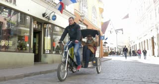 TALLINN, ESTONIA - APRIL 27, 2015: Steadicam shot of two tourists having sightseeing tour in Tallinn in cycle rickshaw.