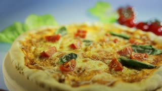 Tasty Italian pizza. Italian food from pizza dough with vegetables, basil, tomato, ingredients. Fresh Italian pizza for dinner. Mediterranean cuisine