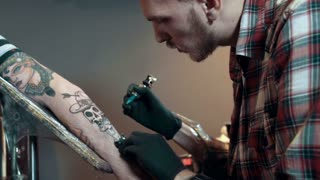 Tattoo artist make tattoo in studio, dolly shot
