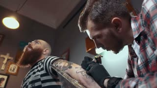 Tattoo artist make tattoo in studio