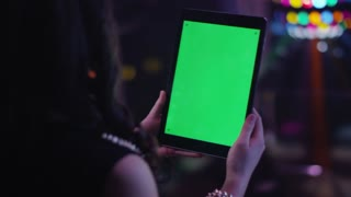 Teen Girl is Holding Tablet PC with Green Screen in Portrait Mode in Nightclub.
