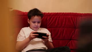 Teenager is playing his portable game console. Middle shot with shallow dof.