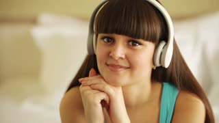 Teenager listening music and looking away with smile