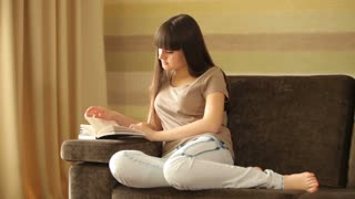 Teenager reading a book and looking at camera