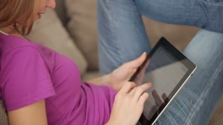Teenager sitting on sofa with touchpad