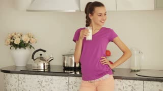 Teenager standing in kitchen and drinking milk