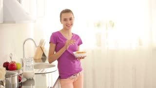 Teenager standing in kitchen and eating cornflakes