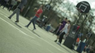 Teenagers playing basketball in a city park. Blured with empty surface in a front.