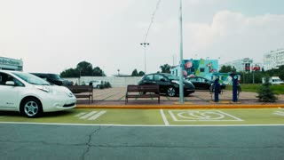 The approaching car to recharge station. Depot for recharging electric cars with two digital charging points in an urban environment conceptual of eco friendly transport. Man getting ready to charge