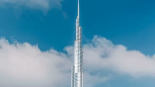 The Burj Khalifa among blue sky with clouds and rays of sun light timelapse, tallest building in the world. Dubai, UAE
