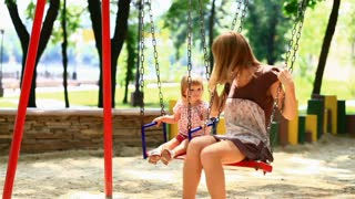 The child and his mother ride on a swing in the park