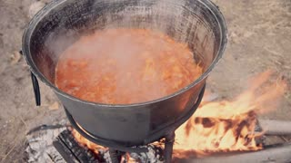The cook stirs slowly the boiling carrot in a cauldron placed on fireplace. Camping food