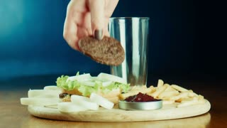 The female puts a hamburger fried French fries and pours coca or soda with ice on a tray. Good for health and unhealth food theme