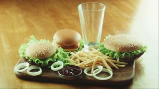 The female puts a hamburger fried French fries and pours coca with ice on a tray. Good for health and unhealth food theme