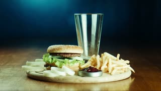 The female puts a hamburger fried French fries and pours cola or soda with ice on a tray. Good for health and unhealth food theme