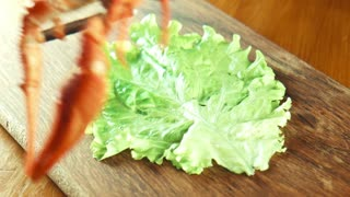 The female puts crayfish of lobsters on a tray on a lettuce leaf