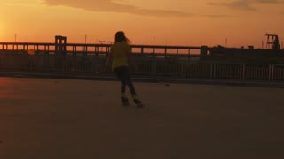 The girl skates on the bridge at sunset