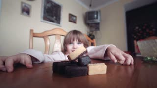 The little girl embraces a hill of chocolates blocks