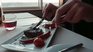 The man with a knife cuts the steak on a plate