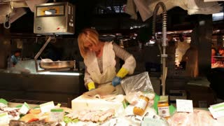 The market fish seller is cutting the fish at the central market on May 27, 2012 in Barcelona, Spain. Part I
