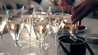 The waiter throws a ice peaces in wine glasses using tongs, Gray table covered with half full glasses. Glasses of white wine for party or wedding