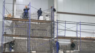 the workers on the scaffolding inside a large and modern warehouse