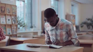 The young African student working in library using a digital pad and the book