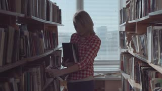 The young blond hair beautiful girl works in library, she sorts and puts books on shelves