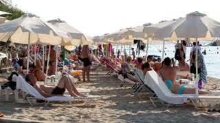 THESSALONIKI, GREECE - AUGUST 23: Crowded summer beach at a tropical resort with beachgoers and holidaymakers relaxing under beach umbrellas on the golden sand on August 23, 2013 in Thessaloniki, Greece