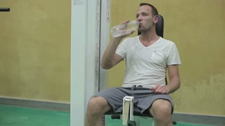 Thirsty man drinking water in a gym