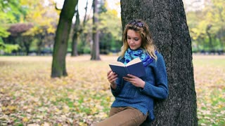 Thoughtful girl reading book and leaning on tree in the park