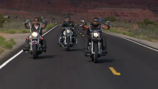 Three Bikers On A Desert Highway, Mesas Behind