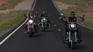 Three Bikers On A Desert Straight Highway
